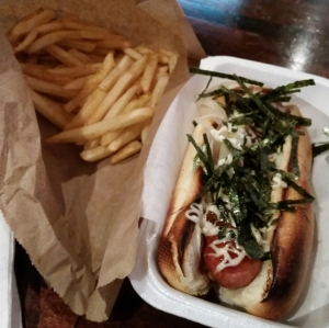 A Kurobuta Terimayo Hot Dog with teriyaki sauce, fried onions, terimayo and crispy seaweed with a side order of sachimi & garlic 'shaked' fries.